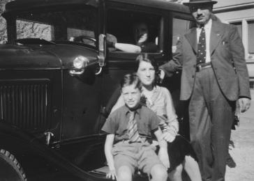 David and Paula Schwab pose in front of a car with their two children Gerd and Margot.