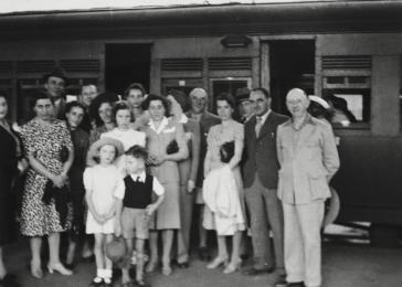 The Berg family is gathered on the platform at a train station in Kenya before their departure for the US.