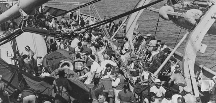 Refugees crowd the deck of a US Army transport