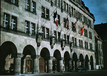 The Palace of Justice in Nuremberg, where the International Military Tribunal trial of war criminals was held. Flags (French, American, British, and Soviet) of the four prosecuting countries hang above the entrance.
