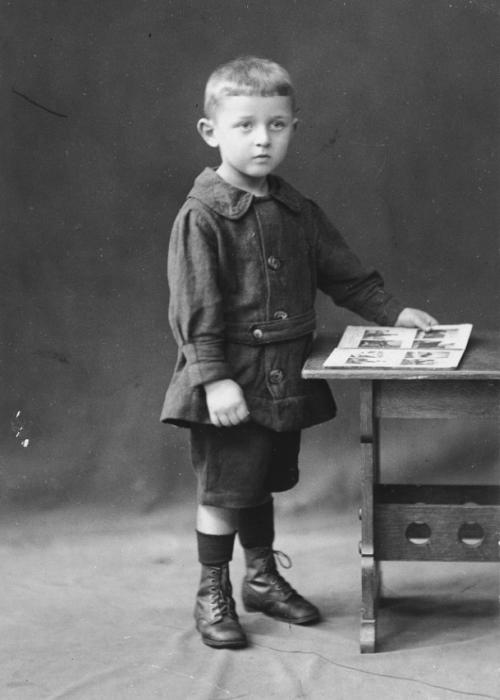 Studio portrait of a young German-Jewish child, Gerd Zwienicki, holding a picture book.