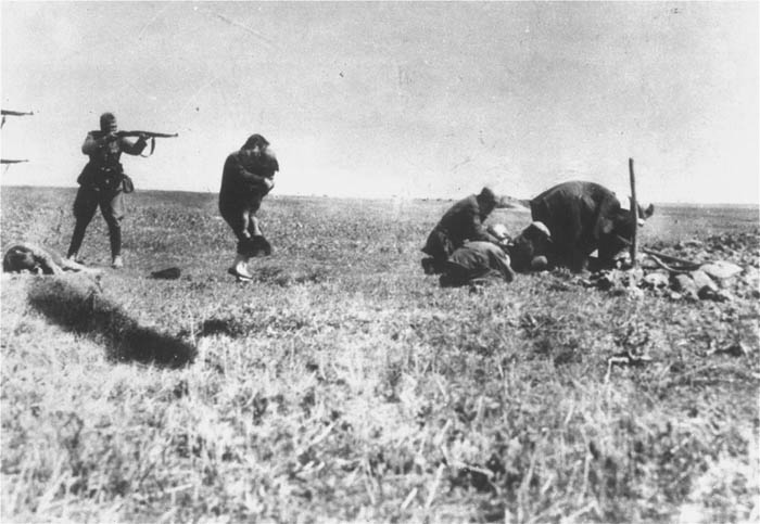 German police take aim at Jews from Ivangorod who have just finished preparing their own grave. Ivangorod, Ukraine, 1941–43.