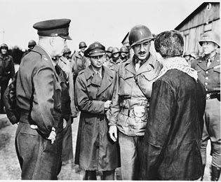 An Austrian-Jewish survivor talks with high-ranking US Army officers in the newly liberated Ohrdruf concentration camp. Among those pictured are General Dwight D. Eisenhower (left) and General George Patton (right)