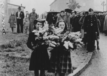 Two Polish women carry wreaths of flowers at a memorial observance after the war. Pictured on the right is Eve Kristine Vetulani.