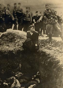 German soldiers of the Waffen-SS and the Reich Labor Service look on as a member of an Einsatzgruppe (mobile killing unit) prepares to shoot a Ukrainian Jew kneeling on the edge of a mass grave filled with corpses.