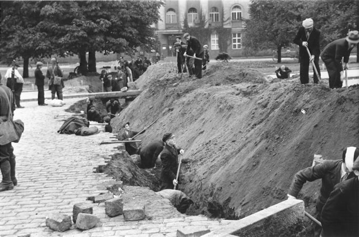 Residents of Warsaw dig a ditch to slow the advance of German tanks in September 1939. American photographer and filmmaker Julien Bryan documented the bombardment of Warsaw and the effect of the extended siege on the city's inhabitants. Smuggling his photos and films out with him, Bryan left Poland in late September during a brief truce that was negotiated to allow citizens of neutral countries to evacuate.
