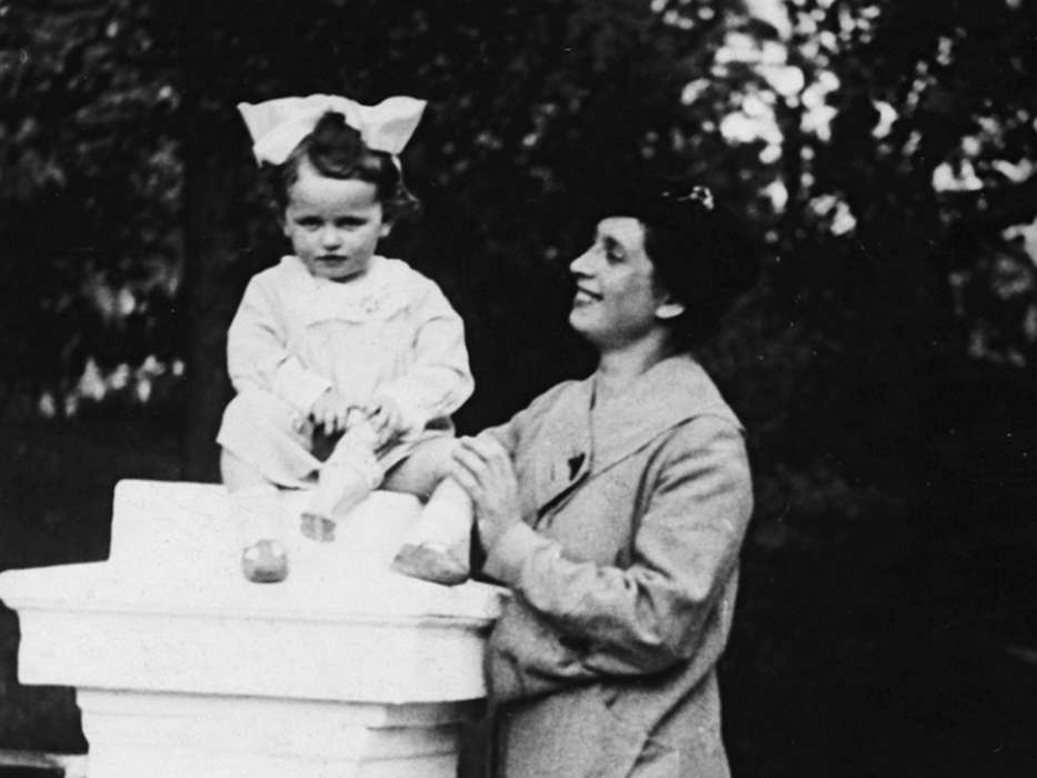 Sala Perec sits atop a pillar as her mother, Bela, stands to the right.