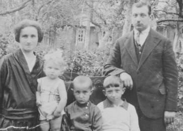 A Lithuanian-Jewish couple poses in the park with their three children. Pictured are Sara, Nesse, Menashe, Yechezkel and Pinchas Galperin.