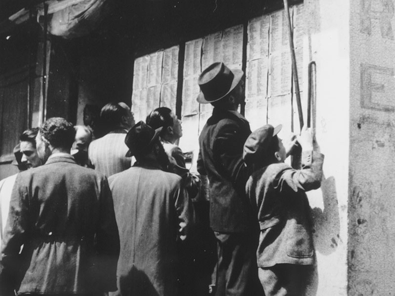 Jewish refugees check the lists of Holocaust survivors that have been posted on the wall of a Jewish-owned bicycle repair shop in Shanghai.