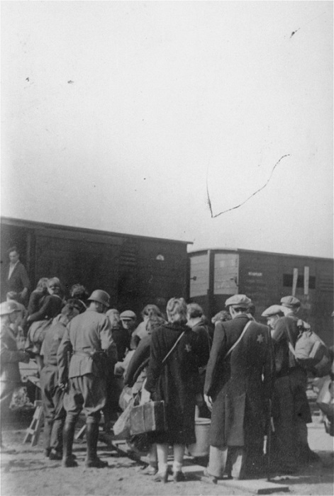 German soldiers guard Lodz ghetto Jews who are boarding a deportation train to Auschwitz, during the destruction of the ghetto in the summer of 1944.