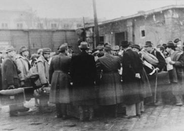 Raoul Wallenberg is present at the Jozsefvaros train station in Budapest where Jews who have been rounded-up for deportation, wait on the platform. Wallenberg stands on the right with his hands clasped behing his back.