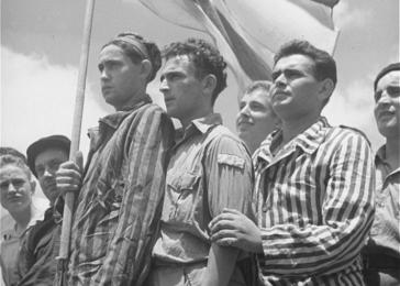 Jewish refugees from Europe aboard the RMS <i>Mataroa</i> hold a Zionist flag as their ship legally enters the port of Haifa, July 1945.