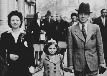 Fajga, Josiane and Jacques Aizenberg walk down a street in Brussels holding hands after being reunited after the war.