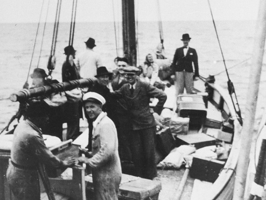 Danish fishermen (foreground) ferry a boatload of Jewish fugitives across a narrow sound to neutral Sweden.