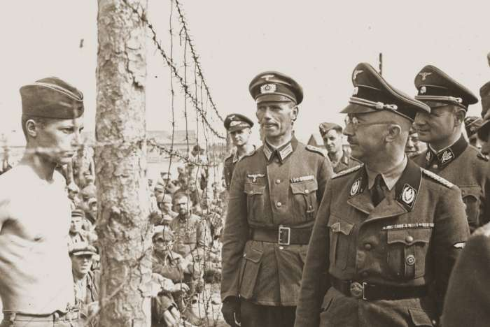 Heinrich Himmler looks at a young Soviet prisoner during an official visit to a prisoner-of-war camp in the vicinity of Minsk.