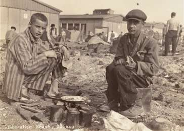 Two survivors prepare food outside the barracks. The man on the right, presumably, is Jean (Johnny) Voste, born in Belgian Congo, who was the only black prisoner in Dachau. Dachau, Germany, May 1945. <i>US Holocaust Memorial Museum, courtesy of Merle Spiegel</i>