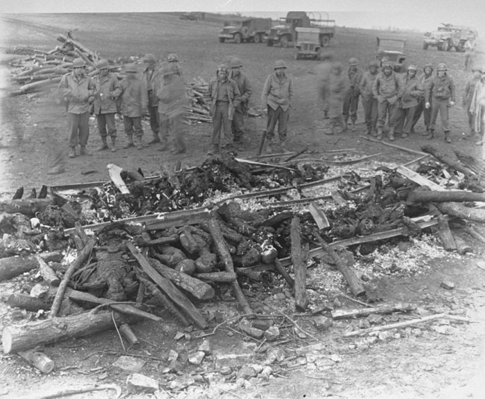 While on an inspection tour of the newly liberated Ohrdruf concentration camp, American soldiers view the charred remains of prisoners burned upon a section of railroad track during the evacuation of the camp. Ohrdruf, Germany, April 4-15, 1945. <i>US Holocaust Memorial Museum, courtesy of National Archives and Records Administration, College Park, MD</i>