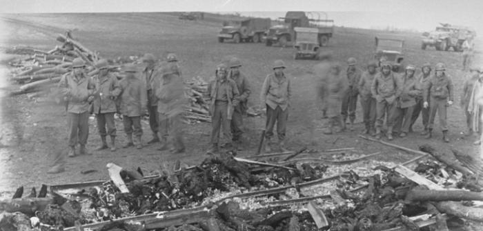 While on an inspection tour of the newly liberated Ohrdruf concentration camp, American soldiers view the charred remains of prisoners that were burned upon a section of railroad track during the evacuation of the camp.