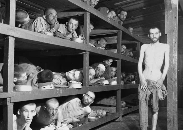 Former prisoners of the &#8220;little camp&#8221; in Buchenwald stare out from the wooden bunks in which they slept three to a &#8220;bed.&#8221; Elie Wiesel is pictured in the second row of bunks, seventh from the left, next to the vertical beam. <i>US Holocaust Memorial Museum, courtesy of National Archives and Records Administration, College Park, MD</i>