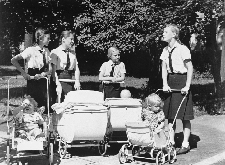 The League of German Girls (Bund Deutscher Mädel), seen taking children to a park, served to educate teenage girls in Nazi beliefs and train them for their roles as wife, mother, and homemaker in German society.&nbsp; <i>Hoover Institution Archives</i>