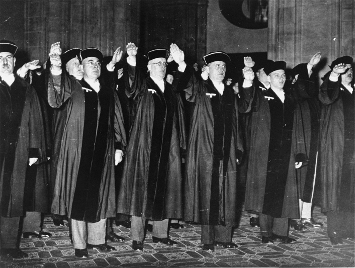 Members of the Berlin criminal court give the Nazi salute on October 1, 1936, the day that judges were required to wear the Nazi eagle-and-swastika emblem on their court robes. <i>Ullstein Bilderdienst, Berlin</i>