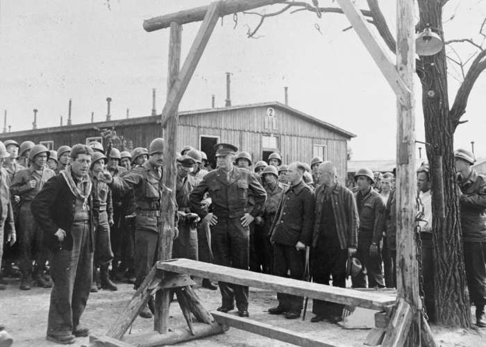 During an official tour of the newly liberated Ohrdruf concentration camp, an Austrian Jewish survivor describes to General Dwight Eisenhower and the members of his entourage the use of the gallows in the camp. Ohrdruf, Germany, April 12, 1945. <i>US Holocaust Memorial Museum, courtesy of National Archives and Records Administration, College Park, MD</i>