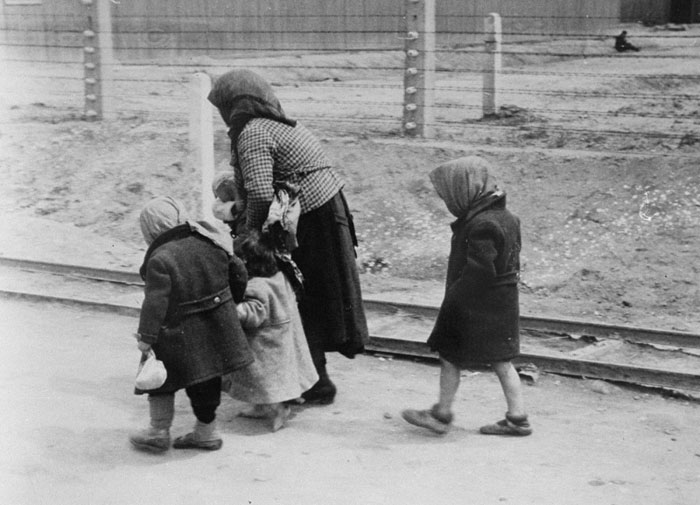 Woman and children walk at Auschwitz