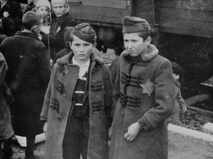 Jewish brothers from Subcarpathian Rus (then part of Hungary) await selection on the ramp at Auschwitz-Birkenau. May 1, 1944.