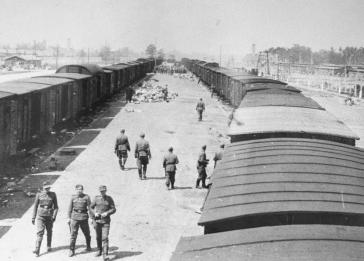SS guards walk along the arrival ramp at Auschwitz-Birkenau.