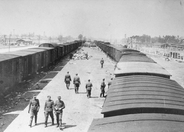 SS guards walk along the arrival ramp at Auschwitz-Birkenau. Poland, May 1944.
