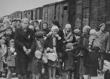 The contrast between the SS female auxiliaries getting off the bus on a day trip in July 1944 and the arrival of a transport of Hungarian men, women, and children in Birkenau in May 1944.