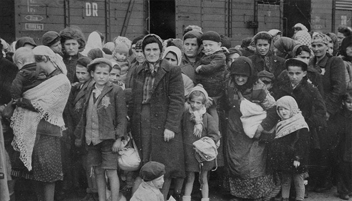 Jewish women and children from Subcarpathian Rus, then a part of Hungary, await selection on the ramp at Auschwitz-Birkenau. 1944.