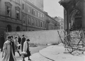Polish civilians walk by a section of the wall that separated the Warsaw ghetto from the rest of the city. Warsaw, Poland, 1940–41.