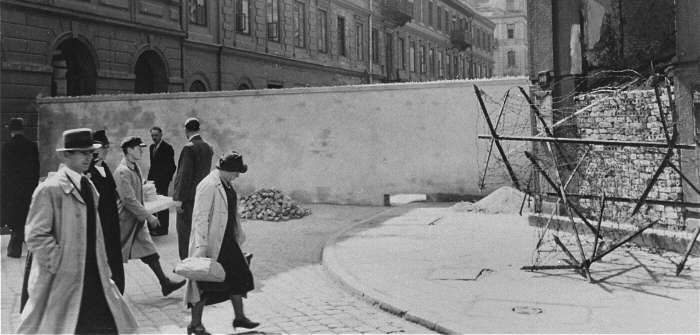 Polish civilians walk by a section of the wall that separated the Warsaw ghetto from the rest of the city. Warsaw, Poland, 1940–1941.