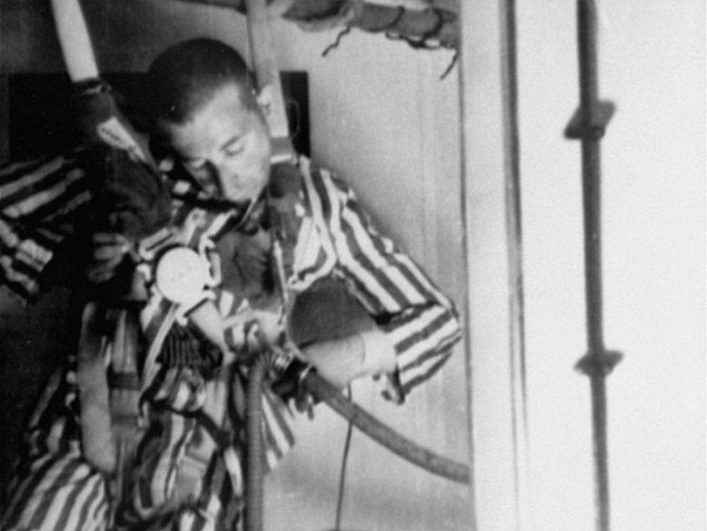 A prisoner in a compression chamber loses consciousness (and later dies) during an experiment to determine altitudes at which aircraft crews could survive without oxygen. Dachau, Germany, 1942.
