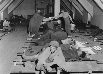 "Survivors from the Mauthausen concentration camp in a temporary hospital at an abandoned Luftwaffe airport. The original US Army caption reads, ""Austria…The Army 121st Evacuation Hospital provides sanitary care for litter cases at an abandoned German airport near Neubau, Austria, where 4,000 prisoners of war were taken after removal from concentration camps."" Neubau, Austria, May 15, 1945."