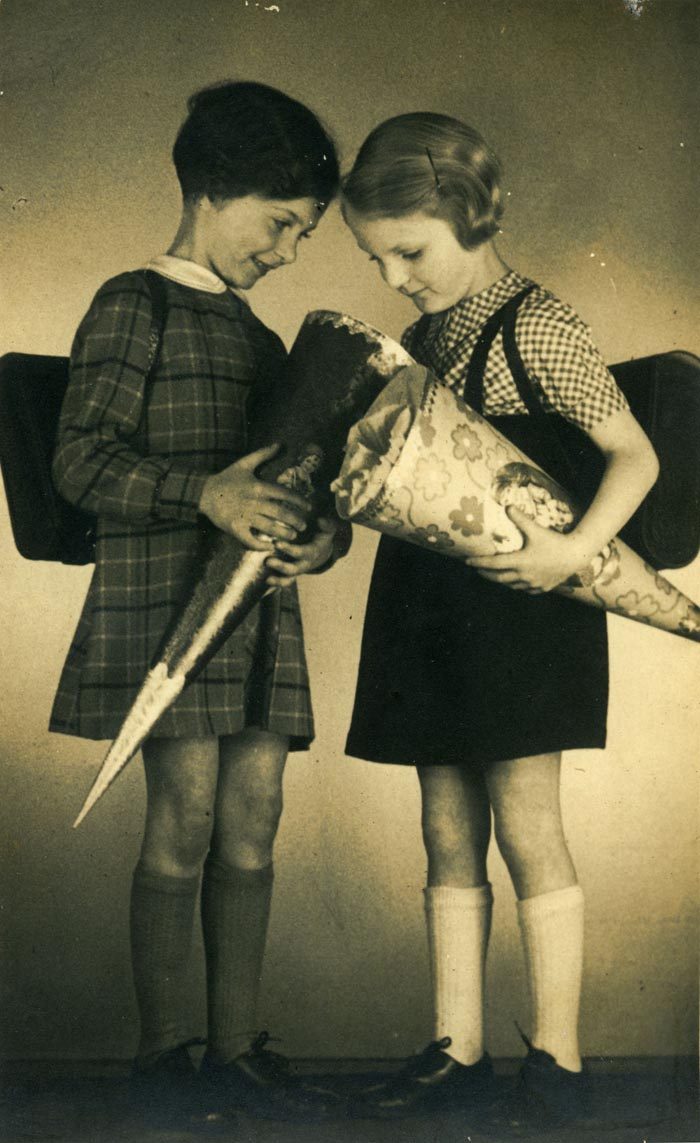 Two Jewish girls (cousins Margot and Lotte Cassel) ready for their first day of school in Breslau, Germany, ca. 1937. Traditional for all children in Germany, the cones are filled with treats to celebrate their first day of school. Margot's father Saul worked in the Teitz department store until he was dismissed following the enactment of the Nuremberg Laws.