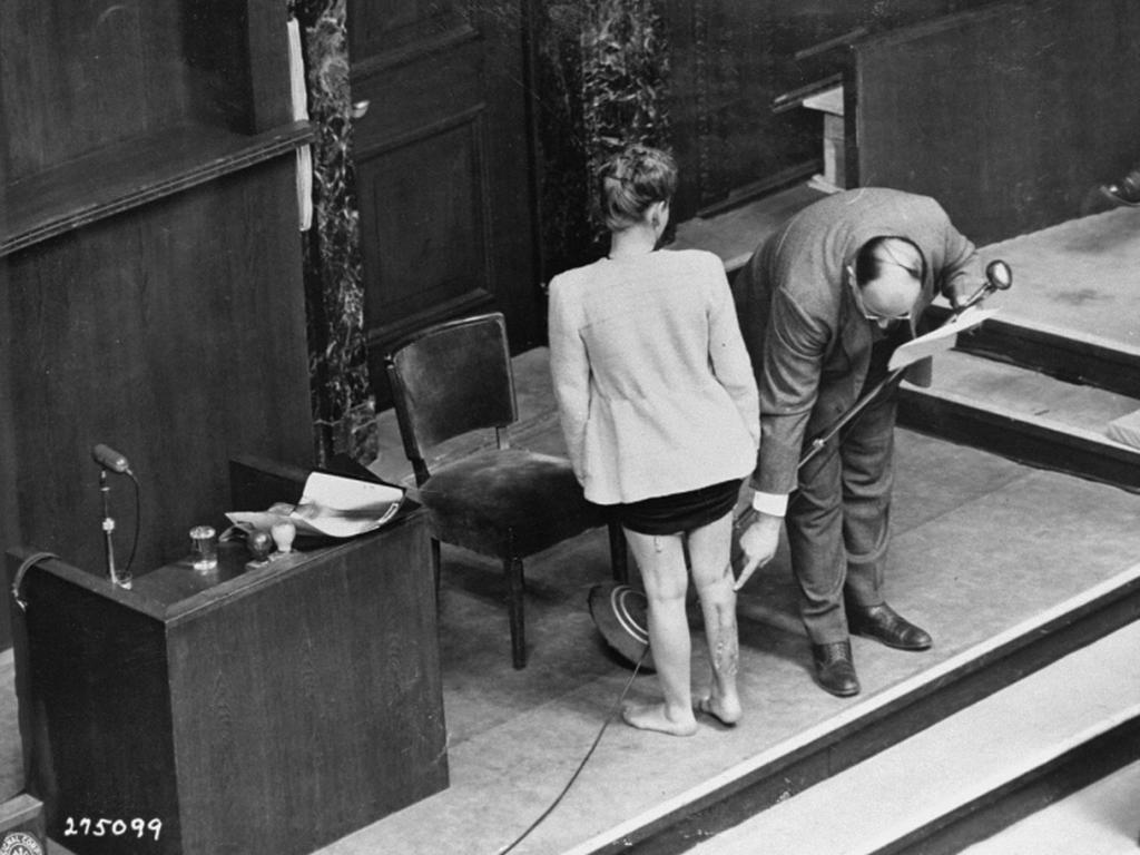 During testimony at the Doctors Trial, American medical expert Dr. Leo Alexander points to scars on Jadwiga Dzido's leg. Dzido, a member of the Polish underground, was a victim of medical experiments at the Ravensbrüeck concentration camp. Nuremberg, Germany, December 22, 1946.
