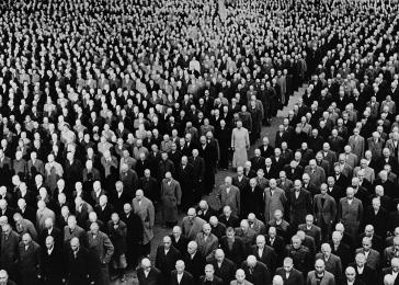 Newly arrived prisoners, with shaven heads, stand at attention in their civilian clothes during a roll call in the Buchenwald concentration camp.