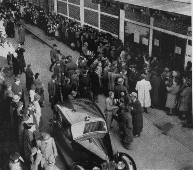 Police attempt to control the crowd of Jews, who are waiting outside a branch of the Swiss legation located in the Glass House on Vadász Street hoping to obtain Schutzbriefe that would protect them from deportation. In the foreground is the car used by Vice Consul Carl Lutz.