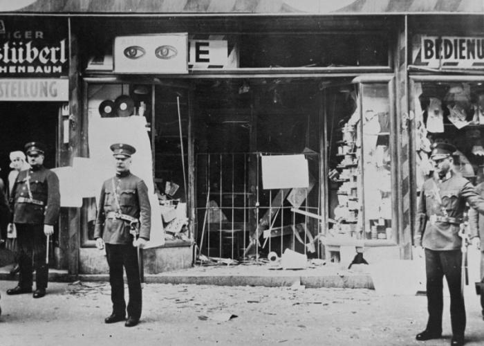 Austrian police stand guard in front of a Jewish-owned business that has been destroyed.