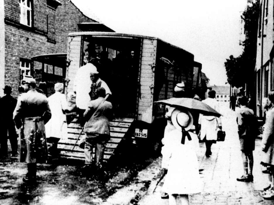 Jews are boarded onto the back of a truck during a deportation action from Kerpen, Germany.