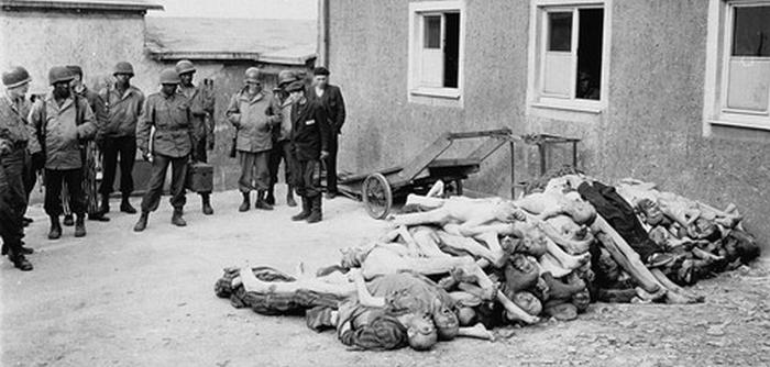 American troops, including African American soldiers from the Headquarters and Service Company of the 183rd Engineer Combat Battalion, 8th Corps, US 3rd Army, view corpses stacked behind the crematorium during an inspection tour of the Buchenwald concentration camp. —US Holocaust Memorial Museum