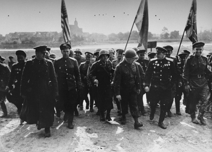 Russian and US First Army soldiers, carrying their respective flags, advance together following their historic link-up at the Elbe River, east of Torgau, Germany.
