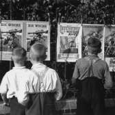 A group of young German boys view Der Stürmer, Die Woche, and other propaganda posters that are posted on a fence in Berlin.