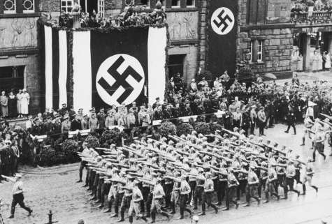 Hitler reviews an SA parade as it passes in front of the Dortmund theater.