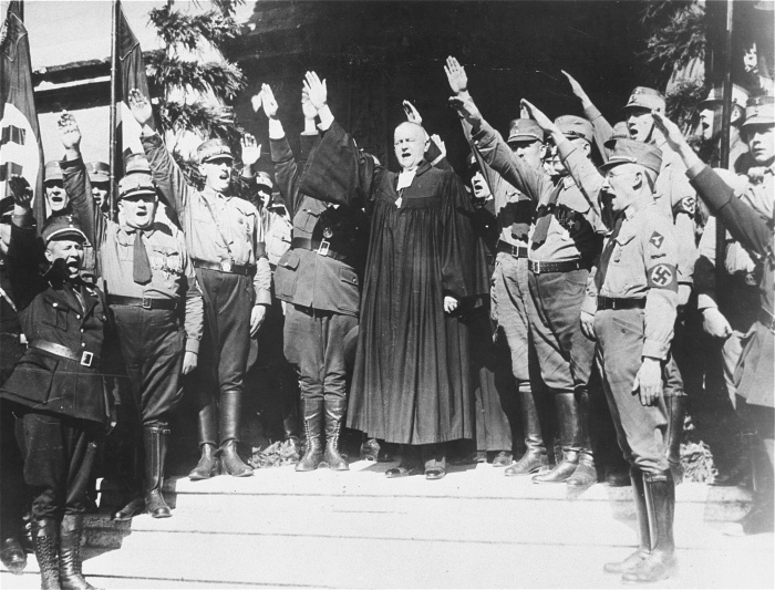 Reich Bishop Dr. Ludwig Müller gives the Nazi salute with a group of SA members at the opening of the national synod at Wittenberg, October 6, 1933. In 1933, Müller was appointed as Reich Bishop with the mandate to unite all Protestant churches into a single, Nazi-controlled organization. While most churches acquiesced to Nazi rule, they resisted unification. <i>Bettman/CORBIS, New York</i>