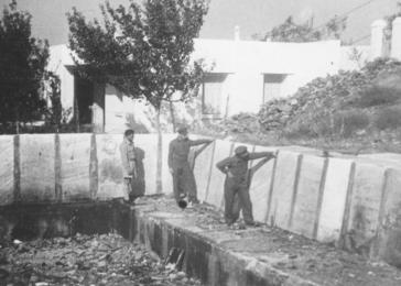 In Salonika, British officers examine a swimming pool constructed by German forces out of Jewish tombstones (1945-46). <i>US Holocaust Memorial Museum, courtesy of Beit Lohamei Haghetaot</i>
