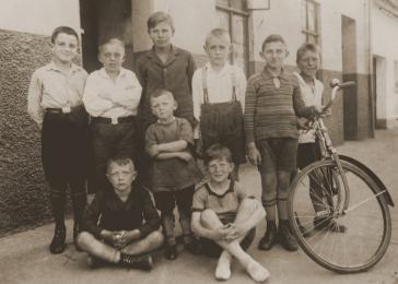 Beno and Gerd Zwienicki pose in front of their father's bicycle shop with a group of non-Jewish children from the neighborhood. One of the German boys later became a guard at the Bergen-Belsen concentration camp.