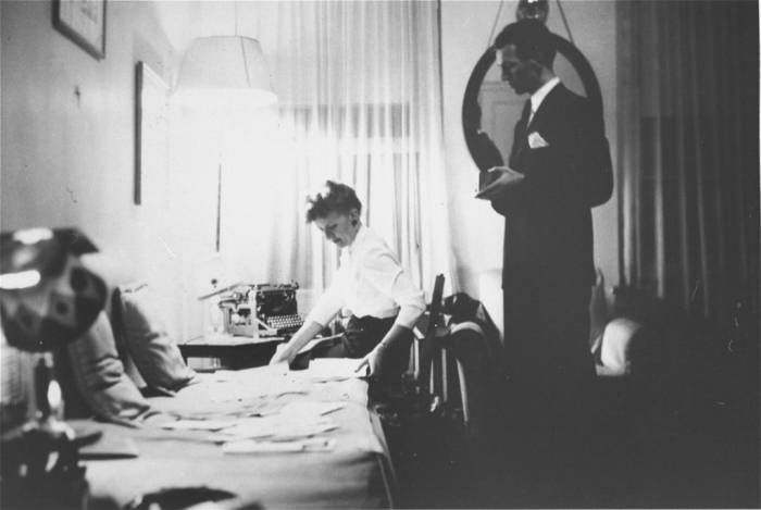 Jan Karski (standing), underground courier for the Polish government-in-exile who informed the west in the fall of 1942 about Nazi atrocities against Jews taking place in Poland. Pictured in his office in Washington, DC, United States, 1944.